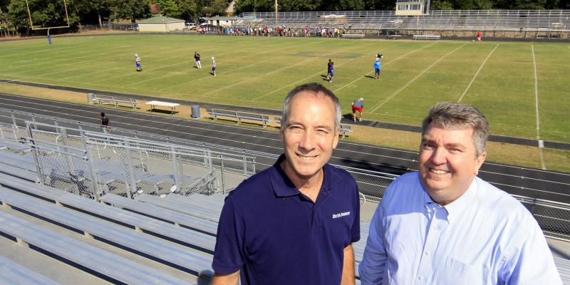Herbi Systems owner, Kenny Crenshaw standing withspecial educator for Elmore Park Middle School and Bartlett High School press box announcer, Ken Carter, in front of the Bartlett High School football field in Bartlett, TN.