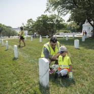 Man and boy kneeling in front of a gravestone at a cemetery at Arlington National Cemetery.
