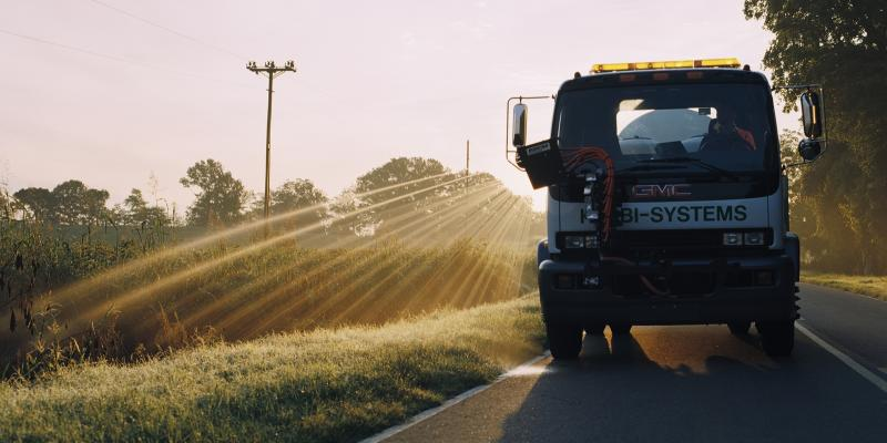 Herbi Systems truck driving down the road with the sun setting behind it while it sprays a field with herbicide.