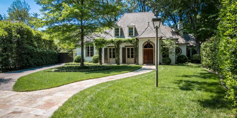 luscious green lawn and trees in front of a white home with dark wood accents. Their lawn has been treated by the lawn care professionals at Herbi Systems